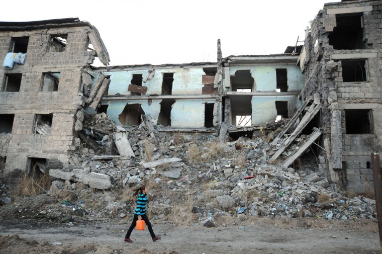 22-year-old Aida carries water past a building left half destroyed by the earthquake in Gyumri, the second largest city in Armenia, around 125 km ( miles) north of Yerevan. (KAREN MINASYAN / AFP/Getty Images)