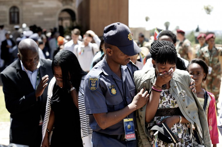 Women are consoled as they react in sadness after walking past the coffin of South African former president Nelson Mandela on the last day of Mandela's lying in state at the Union Buildings in Pretoria on December 13, 2013. (MATT DUNHAM / AFP/Getty Images)