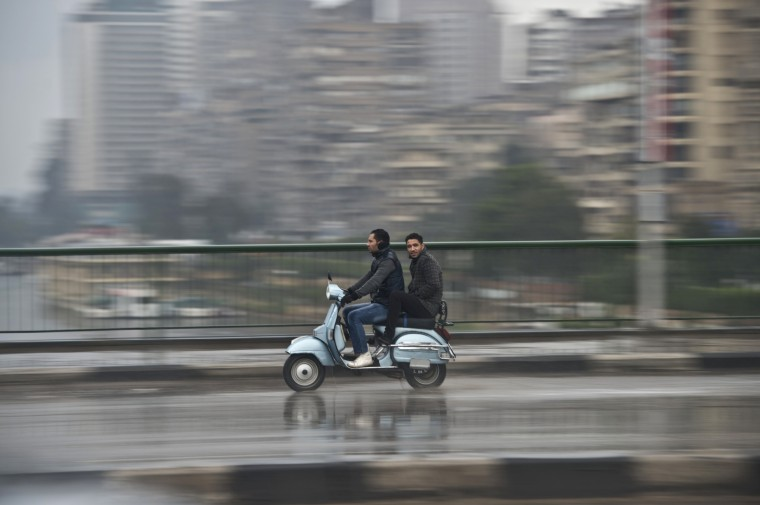 Egyptian men ride a scooter in the rain on December 13, 2013 in the capital Cairo. A regional cold snap spread to Egypt, with some Cairo suburbs seeing snowfall for the first time in years, a weather official said. (Khaled Desouki/AFP/Getty Images)