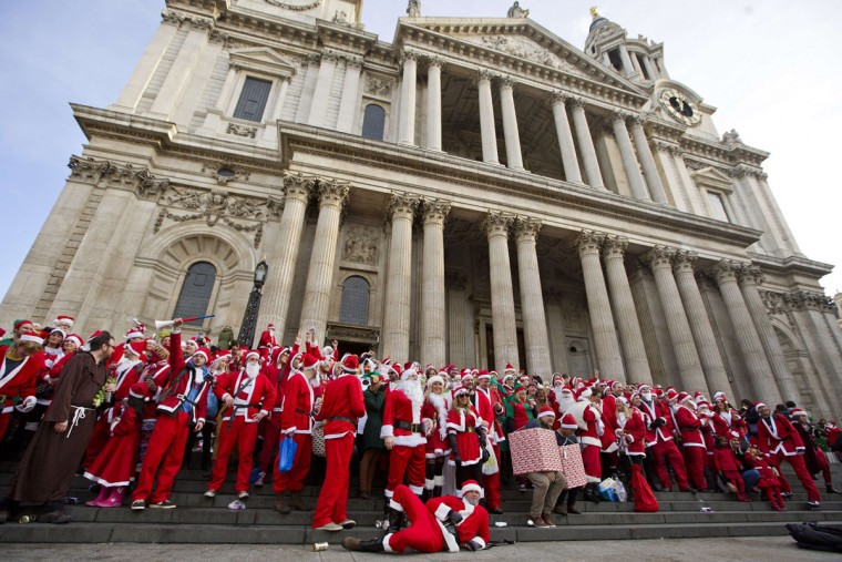 """Revellers in Santa costumes pose for a group photograph as they gather to take part in the annual """"Santacon"""" outside Saint Paul's Cathedral in central London on December 14, 2013. (Justin Tallis/AFP/Getty Images)"""