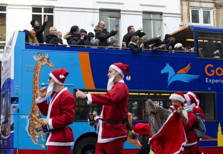 """Passing tourists on a sightseeing bus take photographs of revellers in Santa costumes taking part in the annual """"Santacon"""" in central London on December 14, 2013. (Justin Tallis/AFP/Getty Images)"""