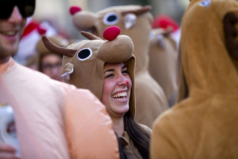 """Revellers in in reindeer costumes gather outside St Paul's Cathedral to take part in the annual """"Santacon"""" in central London on December 14, 2013. (Justin Tallis/AFP/Getty Images)"""