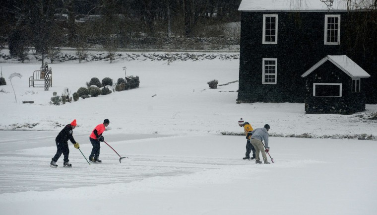 People clear snow from a frozen lake to skate as snow falls in Newtown, Conn. (EMMANUEL DUNAND / AFP/Getty Images)
