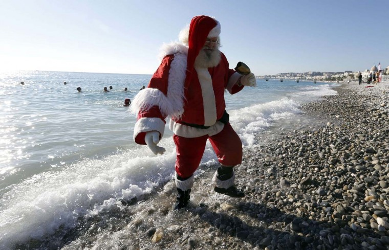 A man dressed as Santa Claus walks on December 15, 2013 on the beach in Nice as part of a traditional christmas winter sea swimming event. (Valery Hache/AFP/Getty Images)