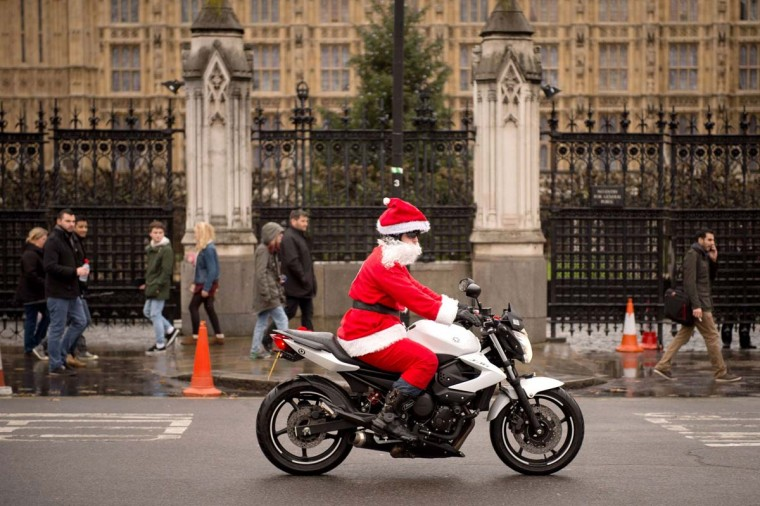 A man dressed as Father Christmas rides a motorbike past the Houses of Parliament in central London on December 15, 2013. (Leon Neal/AFP/Getty Images)