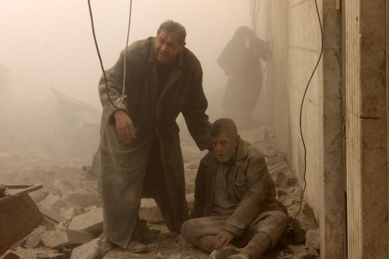 A Syrian man helps an injured man following an airstrike in Aleppo's Maadi neighborhood on December 17, 2013. Two children were among at least 13 people killed in new air strikes on a rebel-held district of Syria's main northern city of Aleppo, the Syrian Observatory for Human Rights said. (Mohammed Al-Khatieb/AFP/Getty Images)