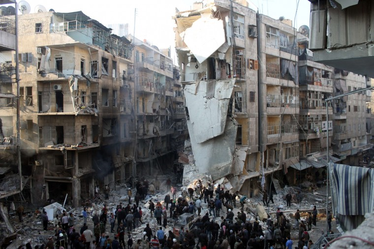 Syrians search for survivors amidst the rubble following an airstrike in the Shaar neighborhood of Aleppo on December 17, 2013. Two children were among at least 13 people killed in new air strikes on a rebel-held district of Syria's main northern city of Aleppo, the Syrian Observatory for Human Rights said. (Mohammed Al-Khatieb/AFP/Getty Images)