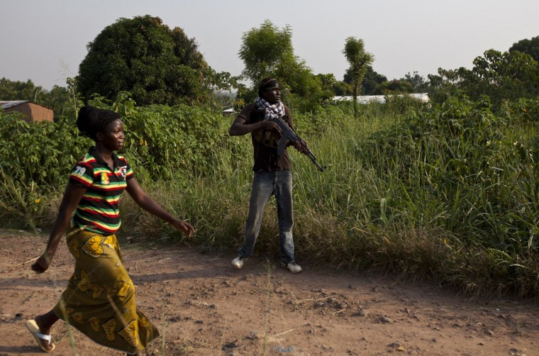 A woman walks by as an anti-balaka militiaman, who was a former member of the Central African Armed Forces (FACA), takes part in a training session on the outskirts of Bangui on December 17, 2013. France today said other European nations would send troops to the Central African Republic to prop up a military force on the ground attempting to disarm militias dispensing deadly violence. The United Nations says some 210,000 people have been displaced in the capital Bangui alone in two weeks of unrest largely pitting Christians against Muslims, and France at the weekend called for more help from its European partners to assist its 1,600 troops on the ground. (Ivan Lieman/AFP/Getty Images)