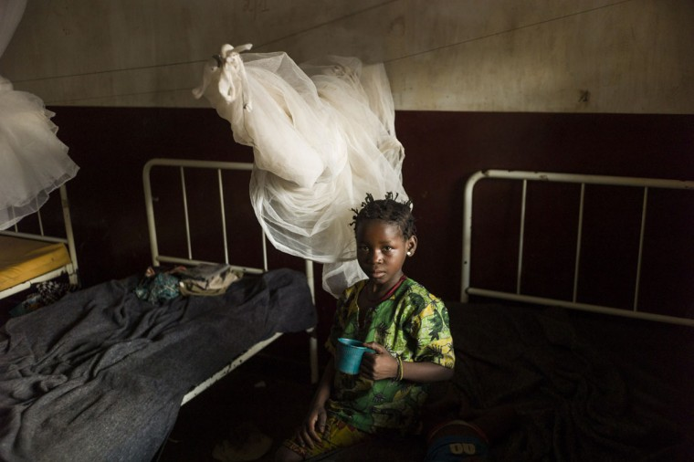 A child helps her brother to drink in her room in the hospital in Bossangoa on December18, 2013. Wrenched apart by sectarian violence, the Central African Republic town of Bossangoa has become little more than a ghost town. (Fred Dufour/AFP/Getty Images)