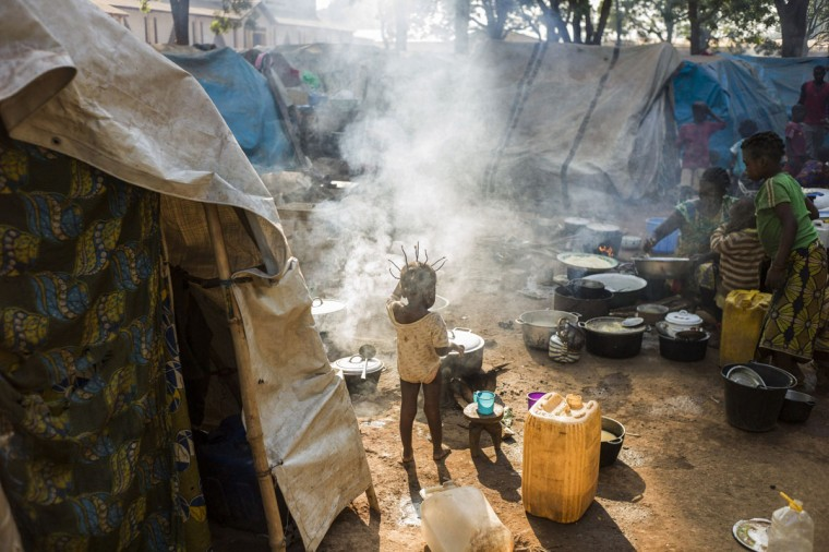A girl stands near a woman cooking in the Christian camp for internally displaced people (IDP) in Bossangoa on December 18, 2013. The Central African Republic's interim president and prime minister were to hold talks on December 18 in a bid to end a political rift, as several European countries offered to help quell deadly sectarian violence in the country. Around 600 people have been killed in less than two weeks, according to the United Nations, while some 210,000 people have been forced from their homes in the capital alone. (Fred Dufour/AFP/Getty Images)