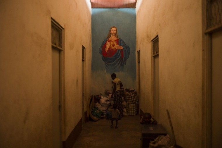 A woman stands in a corridor of a building in the Christian camp for internally displaced people (IDP) in Bossangoa on December 18, 2013. The Central African Republic's interim president and prime minister were to hold talks on December 18 in a bid to end a political rift, as several European countries offered to help quell deadly sectarian violence in the country. Around 600 people have been killed in less than two weeks, according to the United Nations, while some 210,000 people have been forced from their homes in the capital alone. (Fred Dufour/AFP/Getty Images)
