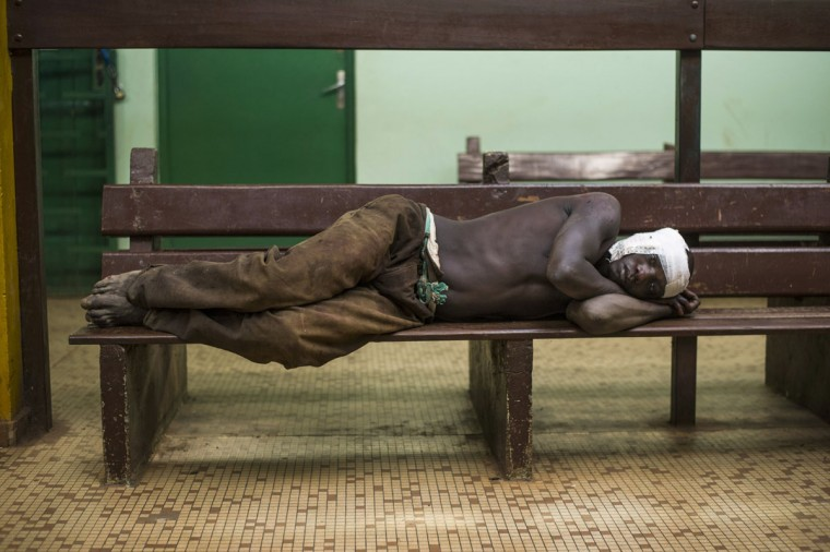 A man wounded during clashes between former Seleka rebels and anti-Balaka militiamen lies with a bandage wrapped around his head on a bench at a hospital in Bangui on December 20, 2013. The Central African Republic has spiralled into chaos since a March coup by the mainly Muslim Seleka rebel group overthrew president Francois Bozize, with deadly violence pitting Muslims against Christians. (Fred Dufour/AFP/Getty Images)