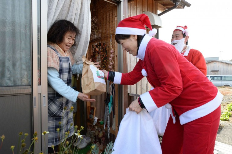 Clad in Santa Claus costumes, volunteers hand Christmas gifts to an elderly woman, who is sheltering from Narahamachi after the accident of a nulcear power plant, in Iwaki, Fukushima Prefecture, on December 21, 2013. Some 100 volunteers delivered Christmas gifts to cheer people living at temporary housings. (Toru Yamanka/AFP/Getty Images)