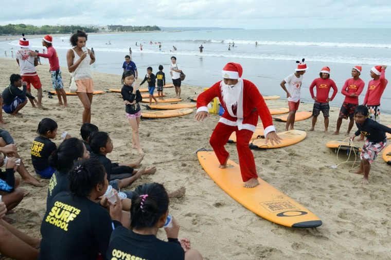 A Balinese surfer dressed in a Santa Claus outfit trains orphan children before they surf on Kuta beach near Denpasar on Indonesia's tourist island of Bali on December 21, 2013. The popular resort island, a pocket of Hindu culture in a country with the biggest Muslim population in the world, receives thousands of tourists every year over the Christmas season. (Sonny Tumbelaka/AFP/Getty Images)