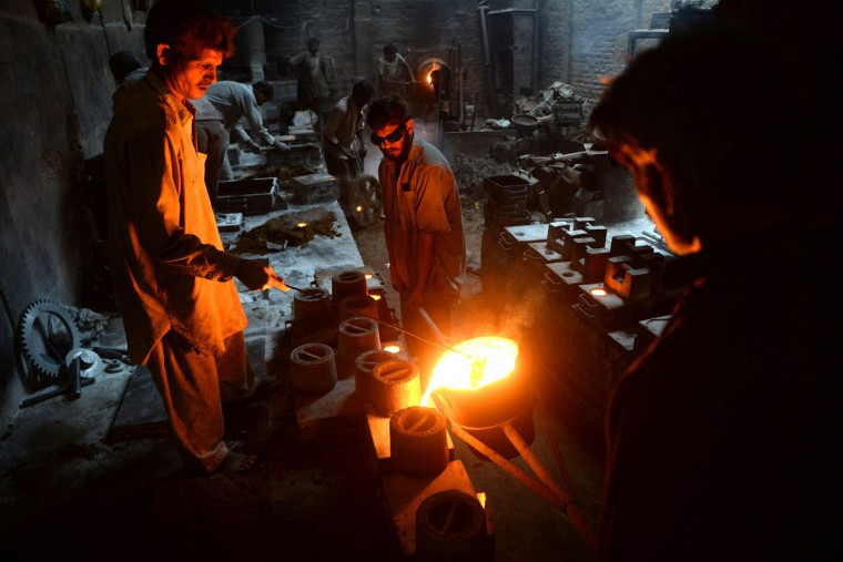 Pakistani labourers work at an iron factory in Karachi on December 21, 2013. Pakistan's has a labour force of 57.2 million, making it the ninth largest country in terms of available human workforce. (Asif Hassan/AFP/Getty Images )
