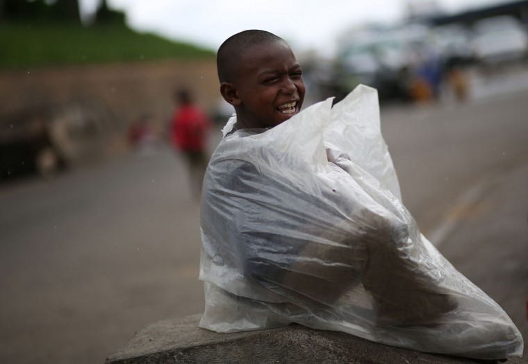 A young child smiles in the rain with his makeshift rain coat and plastic bag in Antananarivo on December 21, 2013 a day after the presidential elections. Madagascar's presidential candidates both claimed victory Saturday in run-off polls, each accusing the other of rigging the run-off as results started to trickle in. (Alexander Joe/AFP/Getty Images)