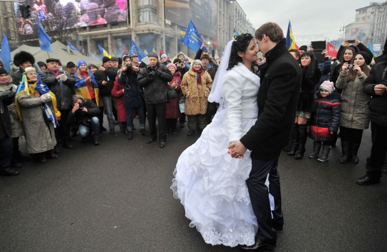 """A just married couple dances on Independence Square as opposition protesters continue to occupy Kiev's central square on December 21, 2013. EU chair Lithuania hit out at Kiev on December 20, saying the European Union remained open to signing a partnership accord with Ukraine but """"not necessarily"""" with Viktor Yanukovych's government. The Ukrainian government last month unexpectedly halted work on key political and free trade agreements with the European Union, sparking the largest demonstrations since the pro-democracy Orange Revolution in 2004. (Genya Savilov/AFP/Getty Images)"""
