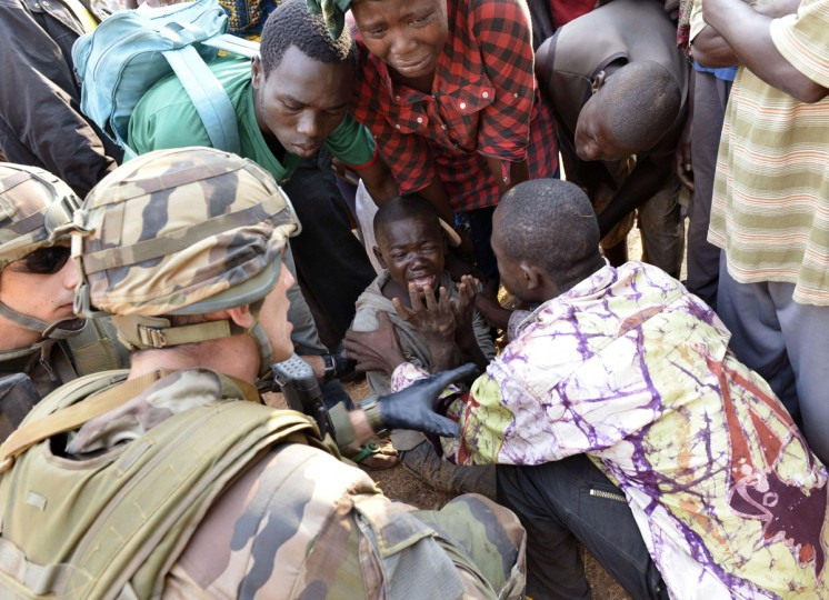 French troops of the Sangaris operation and civilians try to comfort a boy crying after a demonstrator who was shot dead near the international airport in Bangui on December 23, 2013. African Union troops fired on demonstrators protesting against the president of the strife-torn Central African Republic, killing at least one person, according to AFP reporters on the scene. (Miguel Medina/AFP/Getty Images)