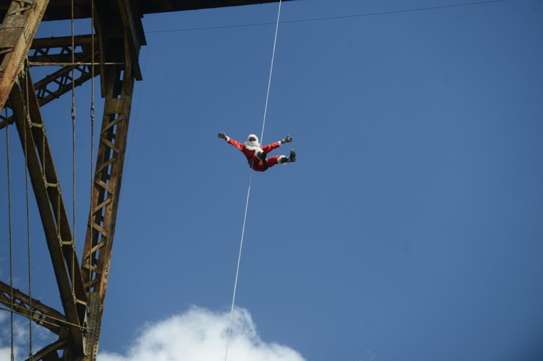 Guatemalan municipal firefighter Carlos Chacon, dressed as Santa Claus, goes down a cable from a bridge to deliver presents to children in Guatemala City on December 22, 2013. (Johan Ordonez/AFP/Getty Images)