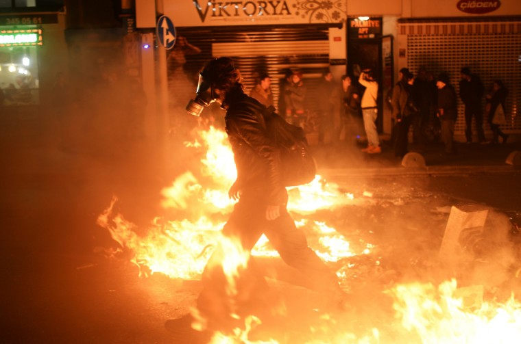 "A man wearing a gas mask walks through fire as protestors clash with Turkish police during a demonstration on December 22, 2013 in the Asian side of Istanbul. Turkey's prime minister threw down the gauntlet to his rivals on Sunday, warning he will ""break their hands"" if they use allegations of high-level corruption to undermine his rule. His heated remarks came as riot police fired tear gas and water cannon to disperse thousands of anti-government demonstrators in Istanbul calling for the government's resignation. ( Bulent Kilic/AFP/Getty Images)"