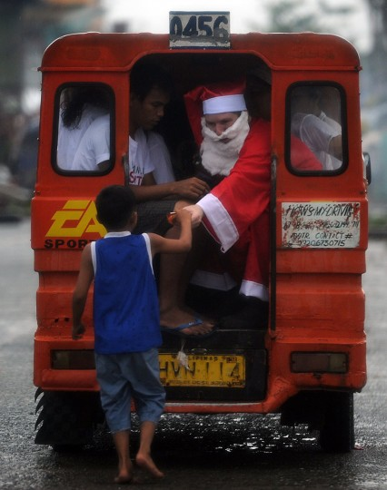 A foreign volunteer dressed as Santa Claus distributes goodies during Christmas to child survivors of the super Typhoon Haiyan in the streets of Tacloban city, Leyte province, on December 25, 2013. Survivors of the Philippines' deadliest typhoon spent a Christmas Day surrounded by mud December 25 as heavy rain drove many inside their flimsy shelters, dampening efforts to retain some holiday cheer in the deeply devout nation. (Ted Aljibe/AFP/Getty Images)