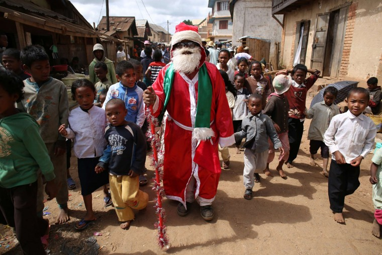 Father Christmas walks in the dusty street of Ambohibary, Madgascar (150 kilometers from the capital Antananarivo), greeting children on December 25, 2013. (Alexander Joe/AFP/Getty Images)