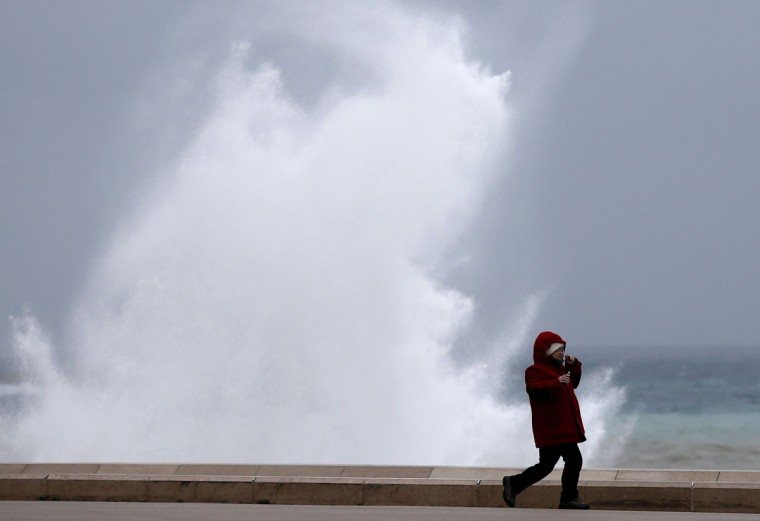 A young person runs in front of a giant wave, on December 25, 2013 in Nice, southeastern France. Gale-force winds and pounding rain Tuesday lashed Britain and France, killing at least five people, disrupting Christmas travel and leaving tens of thousands without power. (Valery Hache/AFP/Getty Images)