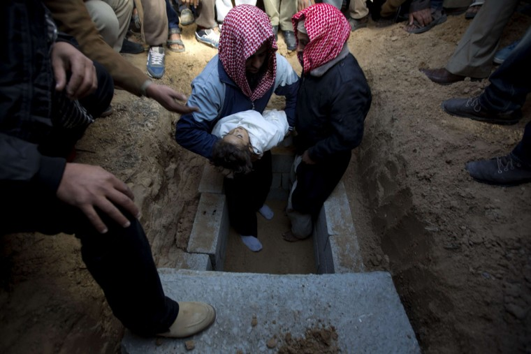 Mourners bury the body of three-year-old Hala Abu Sabakha during her funeral in the central of Gaza Strip, on December 25, 2013. Sabikha was killed, and at least six other people were wounded, in a series of Israeli air and tank strikes on the Gaza Strip, medical sources said. (Mohammed Abed/AFP/Getty Images)