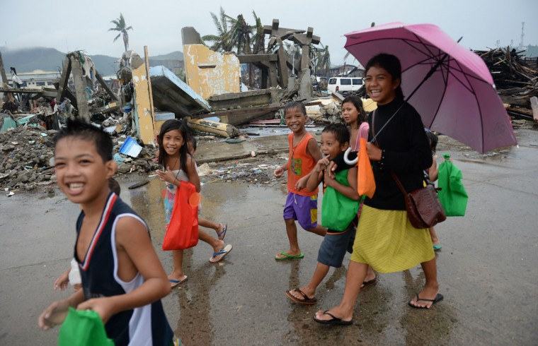 Survivors of super Typhoon Haiyan brave the rain as they walk along the streets to ask gifts from residents in Tacloban city, Leyte province, on December 25, 2013. (Ted Aljibe/AFP/Getty Images)