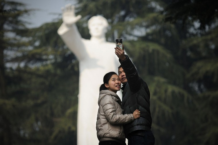 A couple take a photo in front of a statue of former Chinese leader Mao Zedong at a park in Shaoshan, in China's central province of Hunan on December 25, 2013. Thousands of admirers of Communist China's founder Mao Zedong flocked to his home town on December 25 to bow before his graven image -- including one statue of solid gold -- before the 120th anniversary of his birth. (Wang Zhao/AFP/Getty Images)