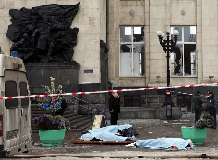 The covered bodies of victims lie on the ground as Russian security personnel inspect the scene of a suicide attack at a train station in the city of Volgograd. (AFP/Getty Images)