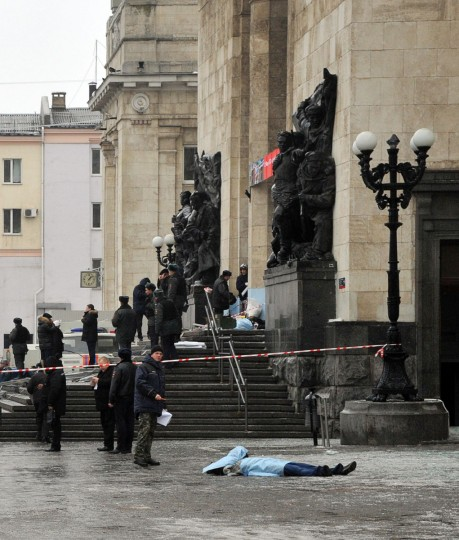 A covered body lies on the ground as Russian security forces inspect the scene of a suicide attack at a train station in Volgograd. (VLADIMIR PAKHOMOV / AFP/Getty Images)