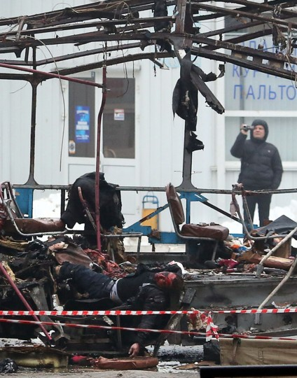 The body of a man lies amid the wreckage of a bus following an attack that destroyed a packed trolley bus. (AFP/Getty Images)