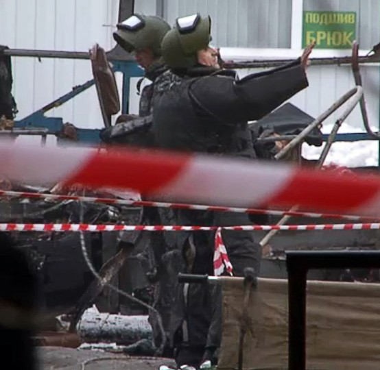 A TV screen grab from VD-TV shows two Russian demolition experts wearing a special gear working near the wreckage of a trolley bus following a suicide attack that killed 14 people in the southern Russian city of Volgograd on December 30, 2013. (AFP/Getty Images)