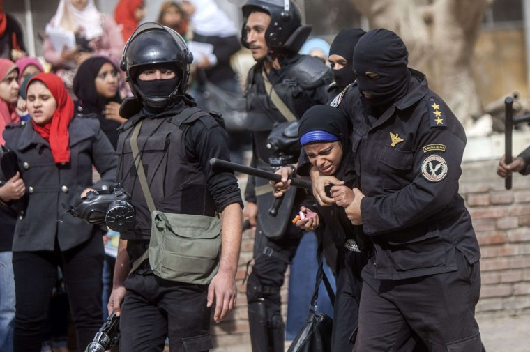 "An Egyptian riot policeman detains a female student of al-Azhar University during a protest by students who support the Muslim Brotherhood inside their campus in Cairo on December 30, 2013. Egypt urged Arab League members to enforce a counter terrorism treaty that would block funding and support for the Muslim Brotherhood after Cairo designated it as ""terrorist"" group. (MAHMOUD KHALED / AFP/Getty Images)"