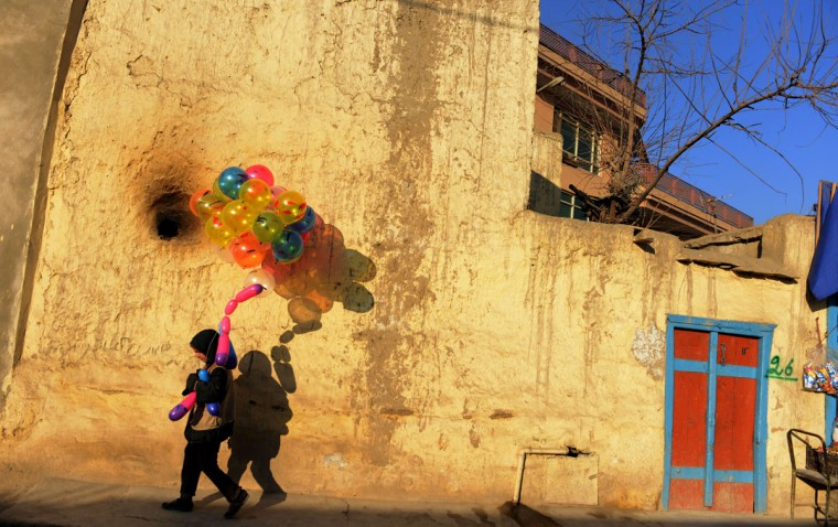 Bashir, an Afghan boy who says he is 5 years old, holds balloons for sale as he walks at a neighborhood in Kabul. (ROBERTO SCHMIDT / AFP/Getty Images)