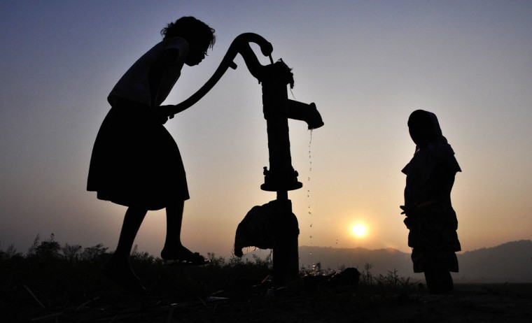 Indian children collect drinking water from a tube-well in the village of Murkata in the Morigoan district on December 30, 2013. (BIJU BORO / AFP/Getty Images)