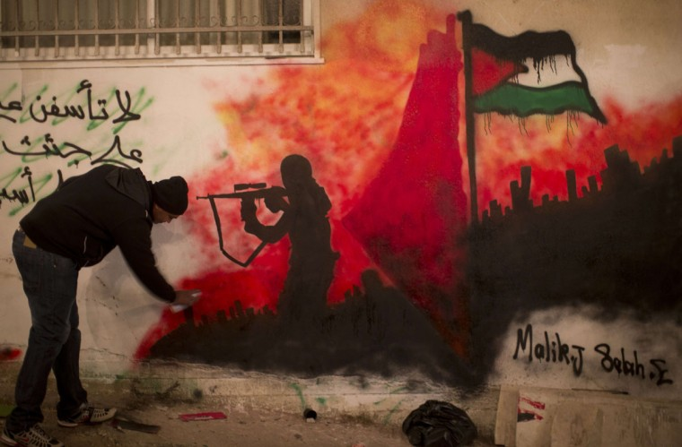 A Palestinian man sprays a mural on a wall near the family home of Palestinian prisoner Ahmad Shehadah in the Qalandia refugee camp near the city of Jerusalem on December 30, 2013. (AHMAD GHARABLI / AFP/Getty Images)