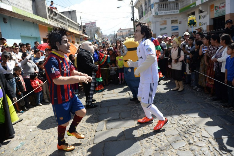 Members of the Saturno group with masks of Barcelona's Neymar (left) and Real Madrid's Gareth Bale parade along the streets of Sumpango, Sacatepequez near Guatemala City on December 30, 2013. The Saturno group is a club whose members try to preserve the traditions of Sumpango. (JOHAN ORDONEZ / AFP/Getty Images)