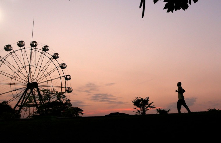 A man is silhouetted against the last sunset of 2013 in the sky above Yangon on December 31, 2013. (Ye Aung Thu/AFP/Getty Images)