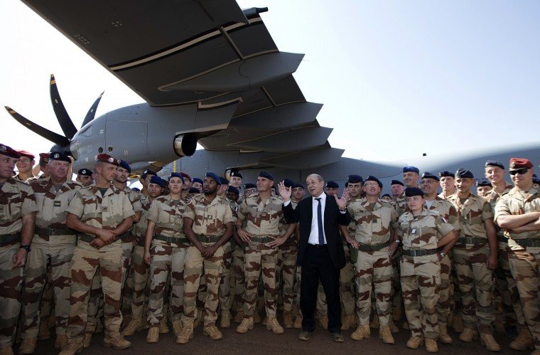 French Defence Minister Jean-Yves Le Drian (C) poses with French soldiers in front of the first A 400M Atlas French military transport aircraft on December 31, 2013, in Gao where he celebrates the New Year, some hours earlier. His visit to Mali is part of a three-day tour focusing on security which also takes in Niger and Chad. France launched Operation Serval in January 2013 to drive out Al-Qaeda-linked extremists who had occupied Mali's north in 2012 and imposed a brutal interpretation of Islamic sharia on the inhabitants of Timbuktu and the other main desert settlements. (Joel Saget/AFP/Getty Images)
