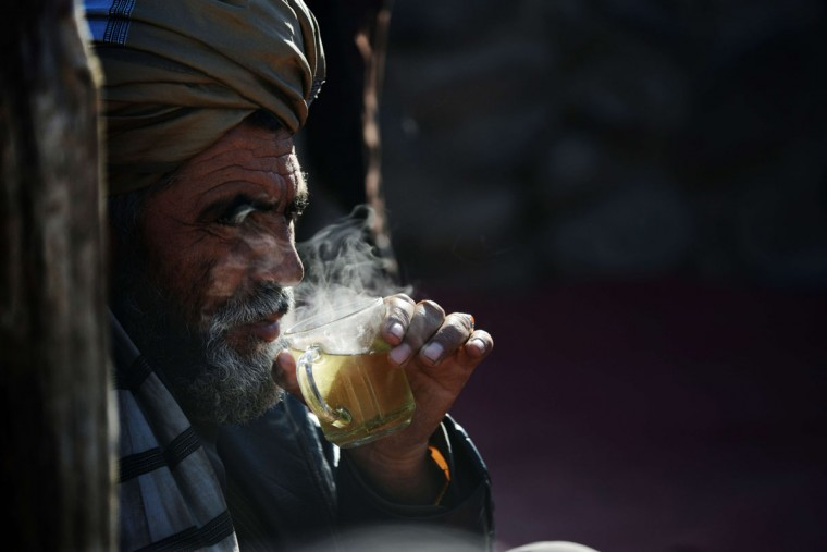 An Afghan man sips tea during a cold winter morning at a livestock market in the outskirts of Kabul on December 28, 2013. Hundreds of traders gather daily at the market to buy, sell and broker buffaloes, sheep, mutton and other cattle. Although the trade at this market remained strong, prices have increased significantly in the last 12 months. (ROBERTO SCHMIDT / AFP/Getty Images)