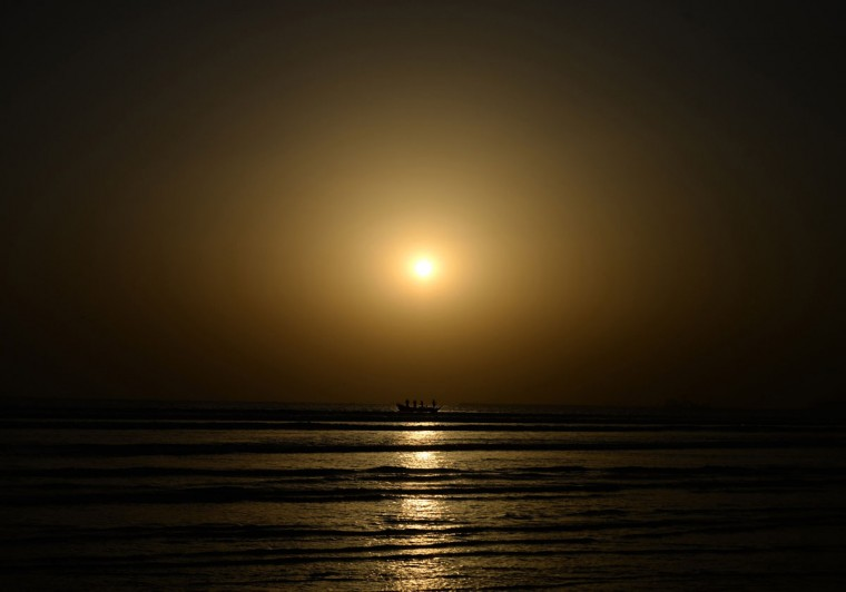 Pakistani fishermen return from the sea during the last sunset of 2013 on New Year's Eve in Karachi on December 31, 2013. People around the world are preparing to welcome 2014. (ASIF HASSAN / AFP/Getty Images)