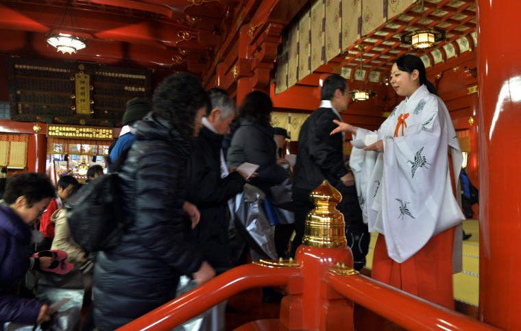 A Japanese Shinto maiden (R) greets worshippers as they enter the Kanda shrine to celebrate the New Year in Tokyo on January 1, 2014. Million of Japanese people visit shrines and temples to pray for the well-being of their families at the New Year. (Yoshikazu Tsuno/AFP/Getty Images)