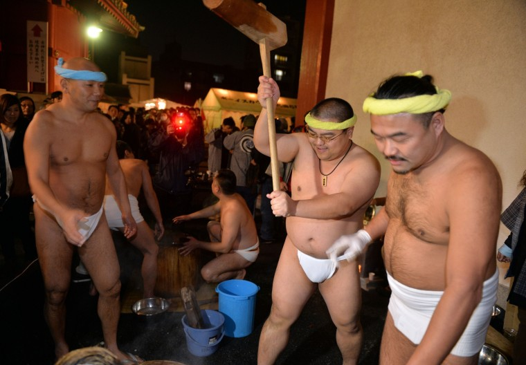 Naked men in loinclothes pound steamed rice into a mochi, rice cake to celebrate the New Year at the Kanda shrine in Tokyo on January 1, 2014. Million of Japanese people visit shrines and temples to pray for the well-being of their families at the New Year. (Yoshikazu Tsuno/AFP/Getty Images)
