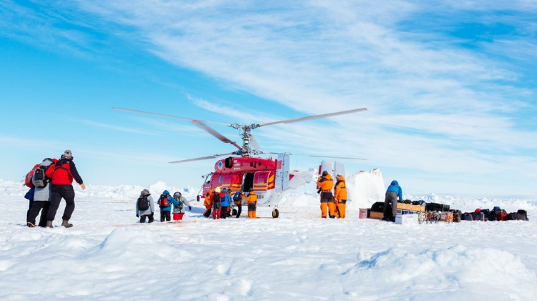 This image taken by expedition doctor Andrew Peacock of www.footloosefotography.com on January 2, 2014 shows a helicopter from the nearby Chinese icebreaker Xue Long picking up the first batch of passengers from the stranded Russian ship MV Akademik Shokalskiy as rescue operations take place after over a week of being trapped in the ice off Antarctica. The helicopter mission to rescue 52 passengers trapped on the icebound Russian research ship finally got underway in Antarctica on January 2 after a number of false starts and failed icebreaking attempts. It was expected to take at least five hours to ferry all passengers from the icebound vessel to the Xue Long -- 10 nautical miles distant -- by helicopter, with five flights of up to 12 passengers and a return journey taking 45 minutes. The ship is carrying scientists and tourists who are following the Antarctic path of explorer Douglas Mawson a century ago, details of which at www.spiritofmawson.com, and have been carrying out the same scientific experiments his team conducted during the 1911-1914 Australian Antarctic Expedition -- the first large-scale Australian-led scientific expedition to the frozen continent. (Andrew Peacock / www.footloosefotography.comAndrew Peacock/AFP/Getty Images)