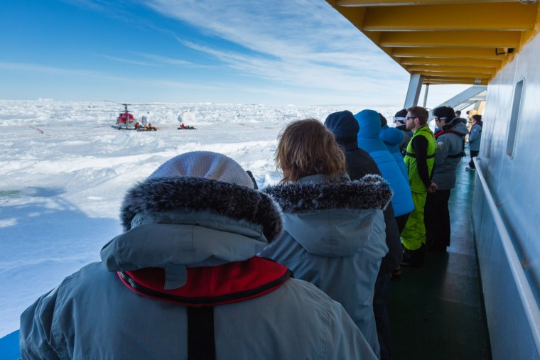 This image taken by expedition doctor Andrew Peacock of www.footloosefotography.com on January 2, 2014 shows passengers on board the stranded Russian ship MV Akademik Shokalskiy watching as a helicopter from the nearby Chinese icebreaker Xue Long picks up the first batches of passengers, as rescue operations take place after over a week of being trapped in the ice off Antarctica. The helicopter mission to rescue 52 passengers trapped on the icebound Russian research ship finally got underway in Antarctica on January 2 after a number of false starts and failed icebreaking attempts. It was expected to take at least five hours to ferry all passengers from the icebound vessel to the Xue Long -- 10 nautical miles distant -- by helicopter, with five flights of up to 12 passengers and a return journey taking 45 minutes. The ship is carrying scientists and tourists who are following the Antarctic path of explorer Douglas Mawson a century ago, details of which at www.spiritofmawson.com, and have been carrying out the same scientific experiments his team conducted during the 1911-1914 Australian Antarctic Expedition -- the first large-scale Australian-led scientific expedition to the frozen continent. (Andrew Peacock / www.footloosefotography.comAndrew Peacock/AFP/Getty Images)