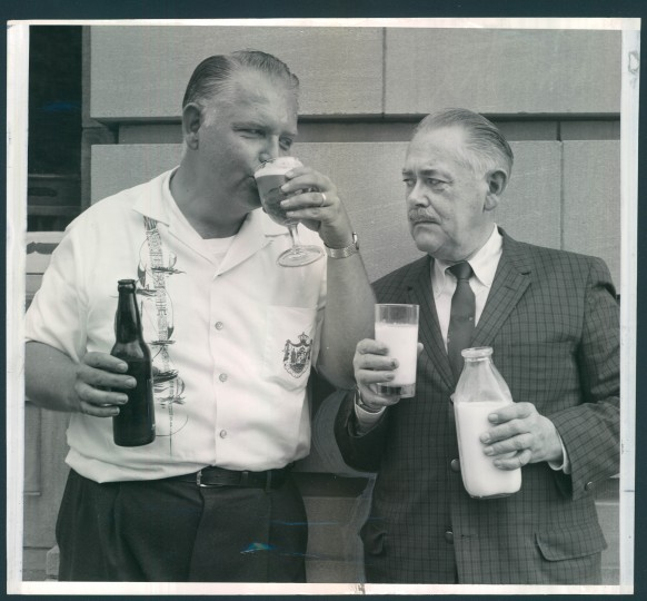 Aza Stanton, left, and Dr. E. Irving Baumgartner symbolize the division that exists in Oakland, Garrett County. The east side of town allows the sale of liquor but the west side is dry. Beer has been legal on both sides since 1935. (A. Aubrey Bodine/Baltimore Sun/July 14, 1961)