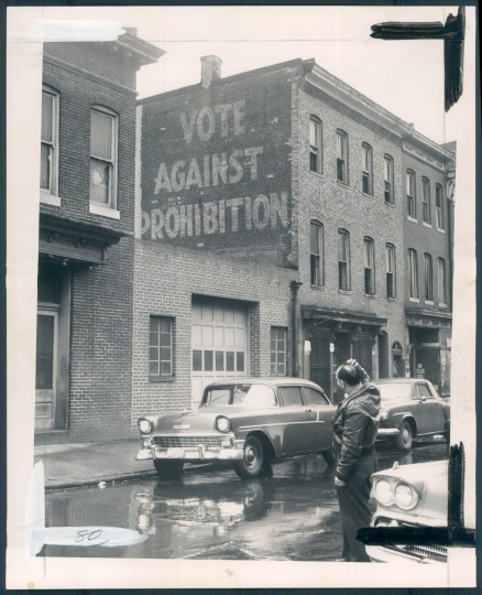 A taxicab driver, looking forward to a busy night as Baltimore prepared for a wide-open celebration of the coming of 1960, paused yesterday on Exeter Street, north of Lexington, and scratched his head at this 26-year-old reminder of things past, before repeal of prohibition made New Year's drinking legal. (Baltimore Sun file)