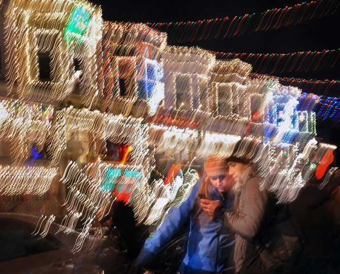 "Jessica Curtis and her boyfriend, Mike Shisler, check their cell phone photos with the lights of the ""Miracle on 34th Street"" display in the background. (Kenneth K. Lam/Baltimore Sun)"